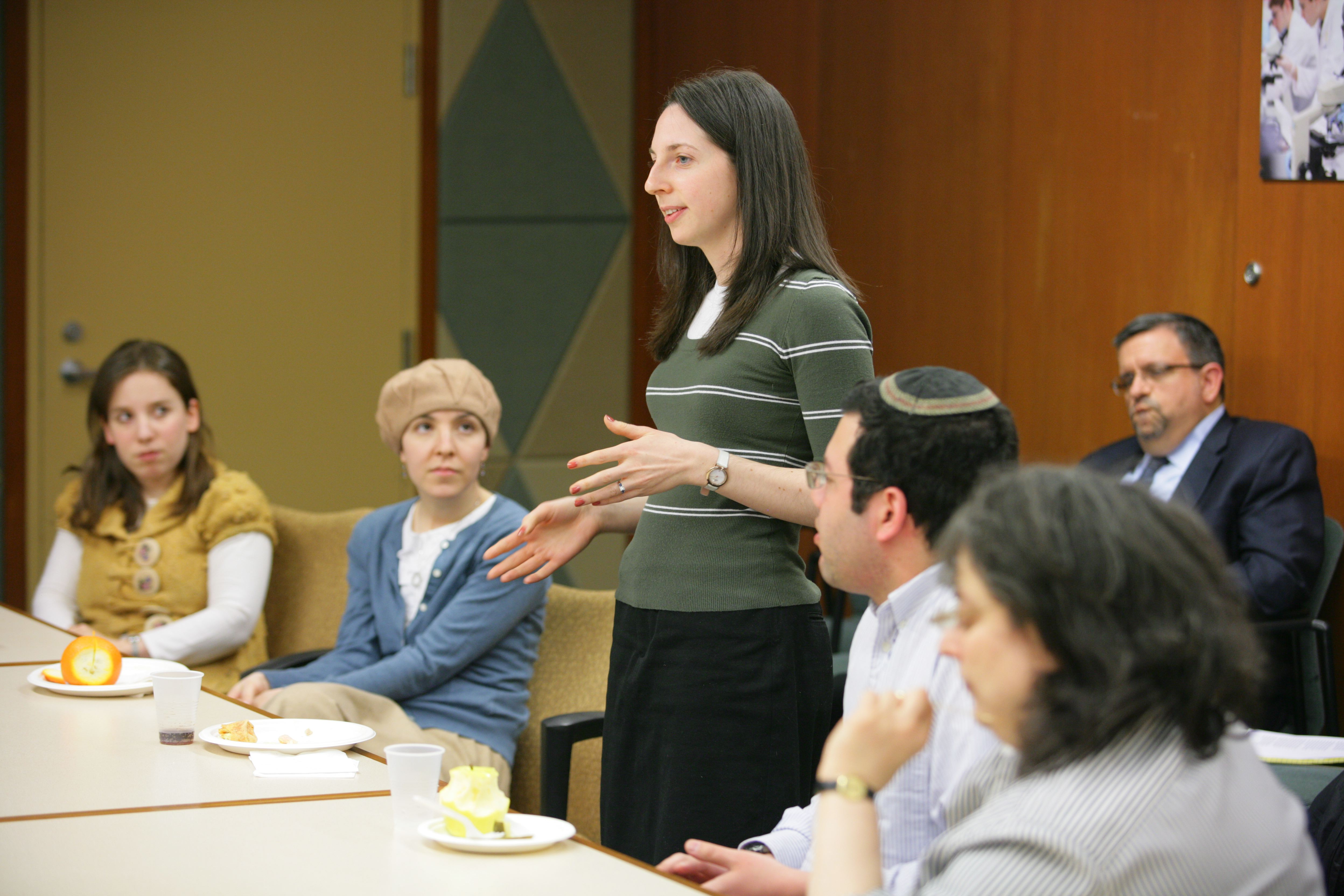 woman standing at table addressing group of students