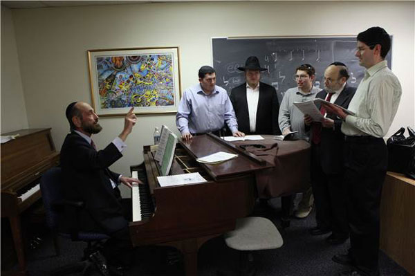 Students and teachers gathered around a piano in Belz School of Jewish Music
