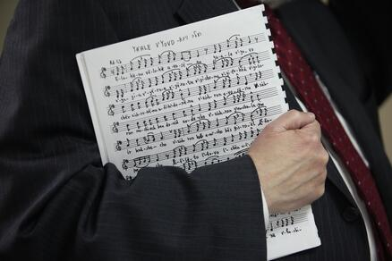 Sheet music held in a man's right arm