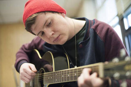 Young man playing guitar in a red hat