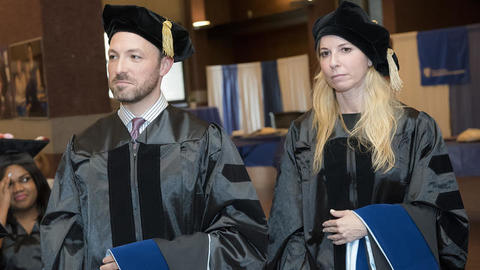 Male and female Wurzweiler sutdents in cap and gown at graduation