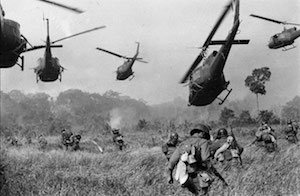 black and white photo from the Vietnam War; soldiers walking through tall grass and 5 helicopters in the air
